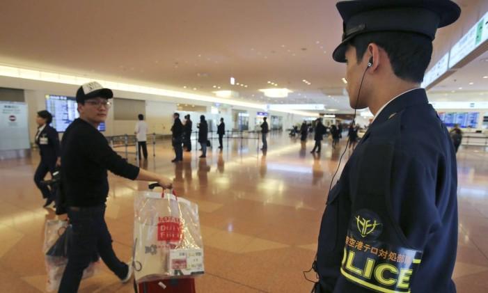 No aeroporto de Haneda, em Tóquio, membro do Departamento de Polícia Metropolitana do Japão observa o trânsito de passageiros Foto: Koji Sasahara / AP