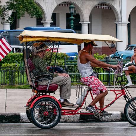 """Um """"bicitaxi"""" leva passageiros em Havana, com uma grande bandeira dos Estados Unidos na traseira, com outra de Cuba, menor, em cima Foto: YAMIL LAGE / AFP"""