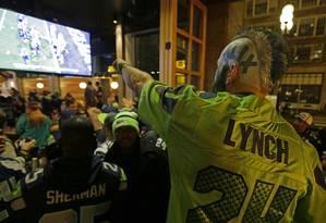 Torcedor assiste à partida de domingo num bar em Seattle Foto: Ted S. Warren / AP