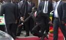 Robert Mugabe tropeça a caminho de pódio em Harare. Queda do presidente do Zimbábue foi negada pelo governo e se transformou em meme na internet Foto: AP