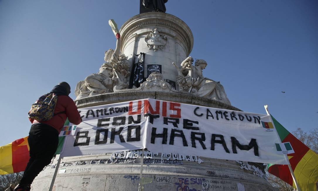 """Camaronesa exilada em Paris ajusta um cartaz com a mensagem """"Camarões unidos contra Boko Haram"""" na Praça da República Foto: Michel Euler/AP /"""