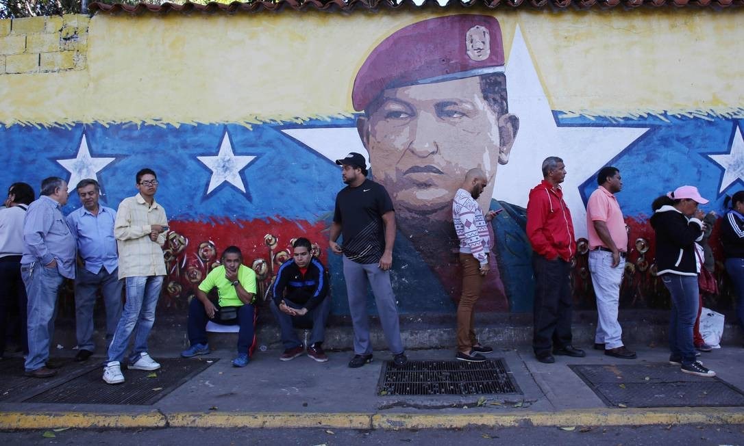 Moradores de Caracas fazem fila diante de uma pintura do rosto de Hugo Chávez: onipresença e culto após a morte Foto: Ariana Cubillos / AP