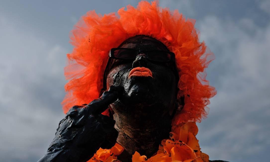 No ano seguinte, um grupo maior se reuniu e saiu em bloco no Sábado de Carnaval, representando uma tribo pré-histórica: enlameados da cabeça aos pés, cobertos de trapos, carregando caveiras, cipós e ossadas Foto: YASUYOSHI CHIBA / AFP