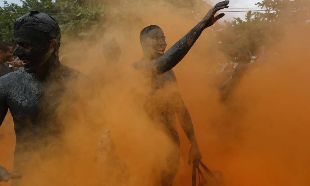 Além da lama, foliões usam pós coloridos na farra Foto: Leo Correa / AP