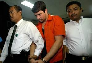 Gularte é conduzido por policiais no dia de sua prisão Foto: AP Photo/5-8-2004 / Dita Alangkara