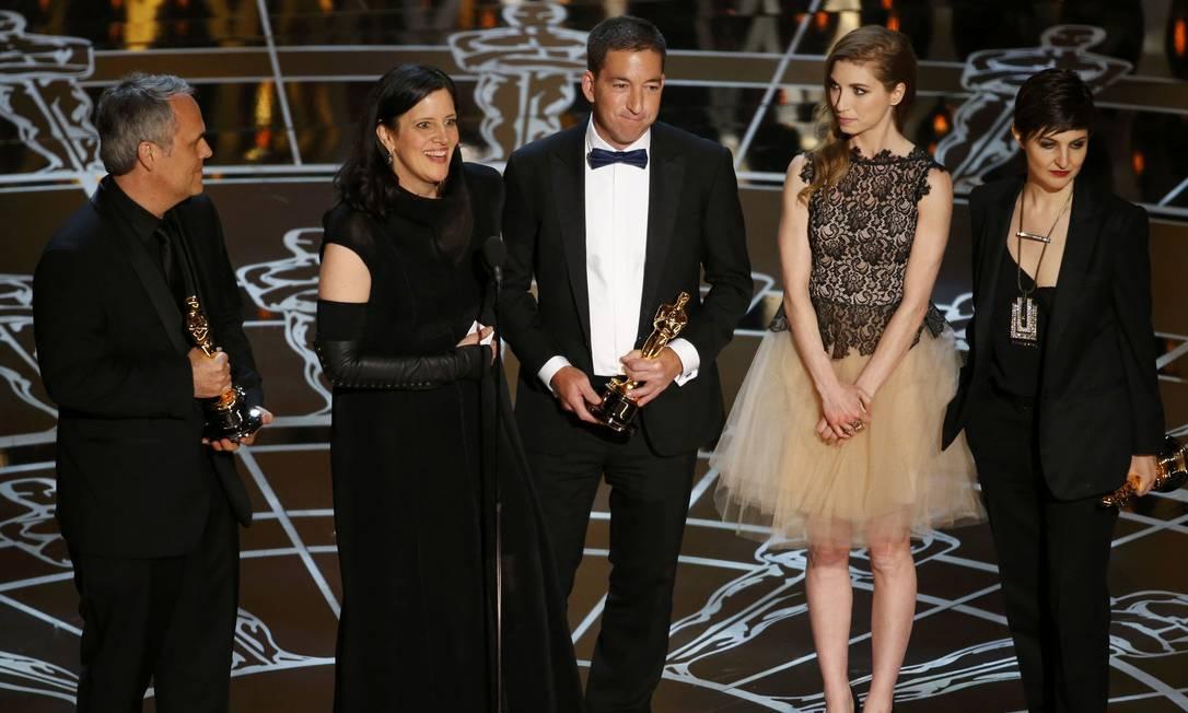Laura Poitras (a segunda à esquerda) agradece o prêmio de melhor documentário para 'Citizenfour'. O Brasil concorria ao prêmio com 'O sal da terra'. 'Citizenfour' conta a história de Edward Snowden, que revelou segredos da NSA, a Agência de Espionagem Americana. 'As revelações de Edward Snowden não afetam apenas a nossa privacidade, mas a nossa democracia', disse a diretora Lauta Poitras. Ela compartilhou o prêmio com Glen Greenwald (que estava no palco) e todos os jornalistas que ajudaram a expor as informações de Snowden. Em uma das reportagens, feita por Greenwald, José Casado e Roberto Kaz no GLOBO, foi revelado que os EUA espionavam telefones e emails de outros países, inclusive o Brasil. Foto: MIKE BLAKE / REUTERS