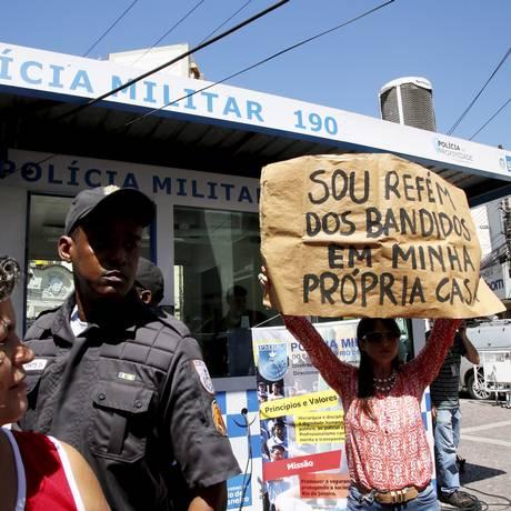 Mulher exibe cartaz durante inauguração de cabine policial no Grajaú Foto: Marcos Tristão / Agência O Globo