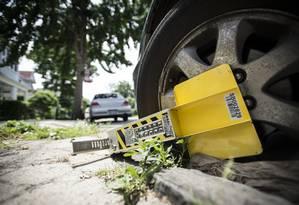 Carro parado em local proibido tem roda lacrada em bairro de Nova York Foto: Robert Stolarik / The New York Times