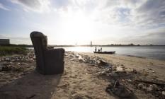 Uma poltrona se destaca em meio à sujeira na Ilha do Fundão: a menos de um ano e meio dos Jogos, estado enfrenta problemas para retirar o lixo da Baía Foto: Antonio Scorza / Agência O Globo