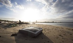 Restos de televisão em meio ao lixo acumulado nas praias da Ilha do Fundão Foto: Antonio Scorza / Agência O Globo