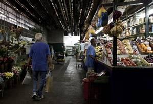 """Entre uma banca de frutas e uma floricultura, consumidor vê um dos poucos corredores que mantiveram a """"alma"""" da Cobal do Leblon Foto: Guilherme Leporace"""