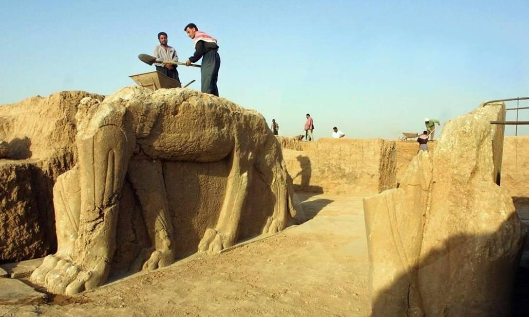 Trabalhadores iraquianos limpam estátua assíria de leão alado em Nimrod em julho de 2001. Ministério iraquiano informou nesta sexta-feira que Estado Islâmico iniciou destruição do sítio arqueológico no Iraque Foto: Karim Sahib