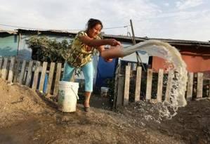 Mulher joga fora água suja em favela nos arredores de Lima, no Peru Foto: MARIANA BAZO / Reuters