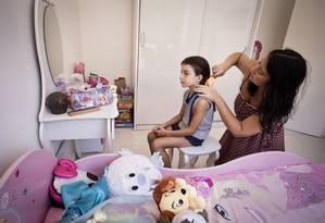 A engenheira Renata arruma a filha Clarice: jornada semanal de trabalho dentro e fora de casa somam 60 horas Foto: Guito Moreto