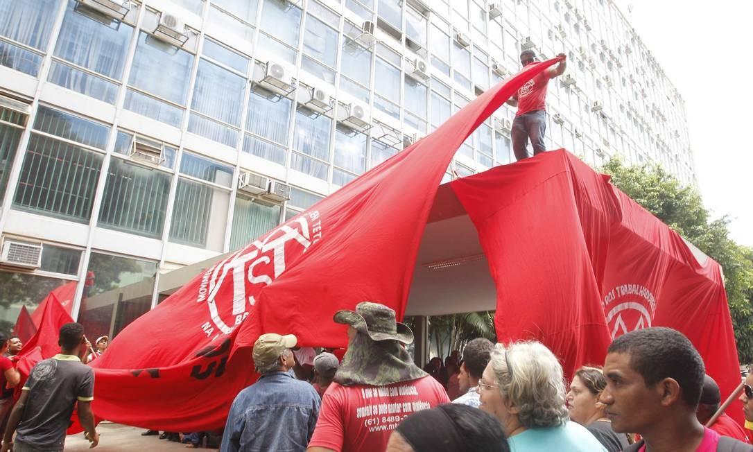Manifestante prega bandeira do movimento no prédio do Ministério da Fazenda Foto: Givaldo Barbosa / Agência O Globo