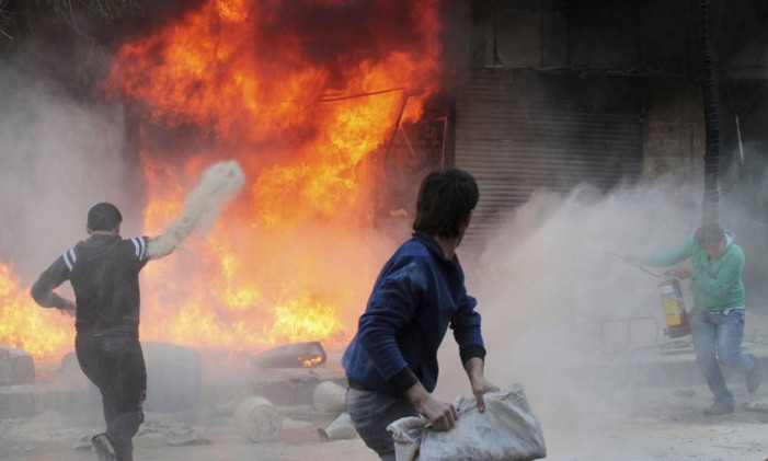 Residents try to distinguish a fire in a gasoline and oil shop in Aleppo's Bustan Al-Qasr neighbourhood October 20, 2013. REUTERS/Aref Hretani (SYRIA - Tags: DISASTER) Foto: AREF HRETANI / REUTERS