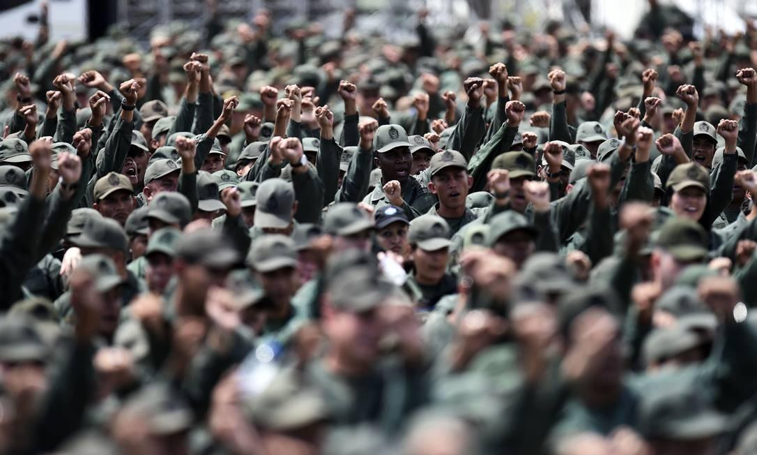 Integrantes da milícia bolivariana e da reserva do Exército erguem os punhos cerrados numa saudação em Caracas. Foto: JUAN BARRETO / AFP