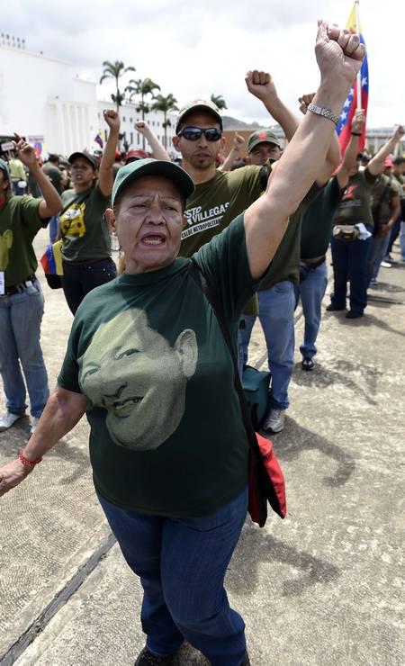 Vestindo uma camisa com o rosto de Hugo Chávez, uma mulher, integrante da milícia bolivariana, ergue o punho cerrado numa saudação em Caracas. Foto: JUAN BARRETO / AFP
