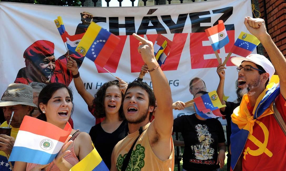 """Diante de uma faixa onde se lê """"Chávez vive"""", jovens seguram bandeiras da Venezuela e do Paraguai numa manifestação em frente à Embaixada dos EUA em Assunção. Foto: NORBERTO DUARTE / AFP"""