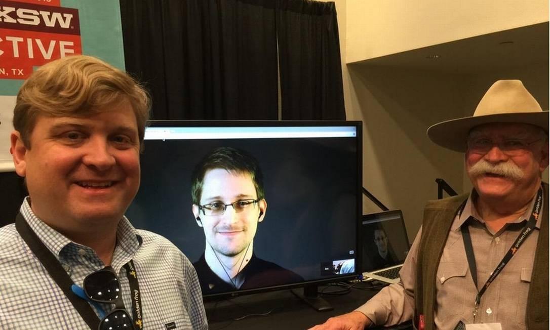 Sunday e Ron Yokubaitis ladeando a tela em que Snowden conversou remotamente com a audiência na reunião fechada Foto: Reprodução / Golden Frog via Twitter http://goo.gl/bKTqTe