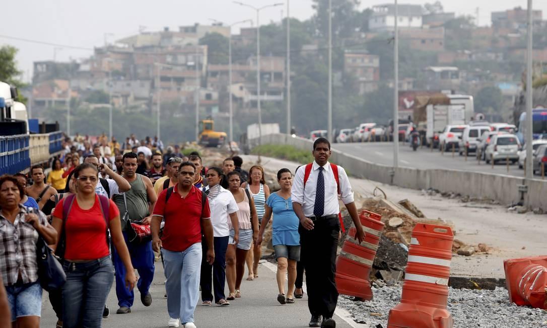 Passageiros que seguiam de ônibus para o Rio tiveram que descer e caminhar pela via Foto: Hudson Pontes / Agência O Globo