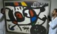 Técnicos do museu Oscar Niemeyer com obra que seria gravura de Miró, e não uma pintura