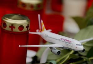 Modelo de um avião da Germanwings entre flores e velas em homenagem às vítimas em Colônia Foto: WOLFGANG RATTAY / REUTERS