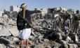 Armas e ruínas. Homem porta metralhadora sobre os destroços de um ataque aéreo próximo do aeroporto de Sanaa