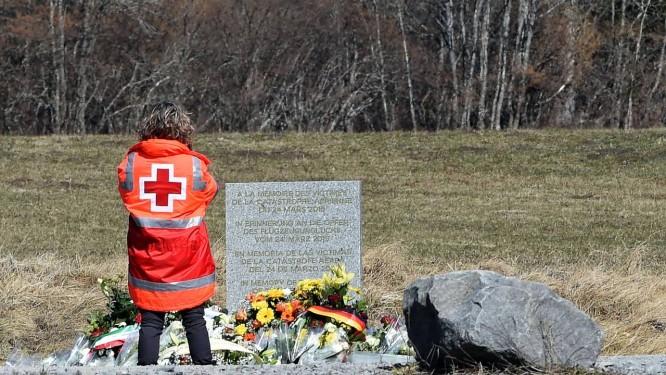 Membro da Cruz Vermelha presta homenagem no memorial às vítimas do desastre aéreo da Germanwings. Companhia ofereceu auxílio a familiares dos passageiros mortos no desastre Foto: BORIS HORVAT / AFP