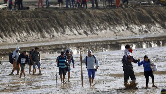 Moradores da região de Copiapó atravessam área inundada nos arredores do rio Chanaral. Número de mortos na tragédia chegou a nove Foto: IVAN ALVARADO / REUTERS