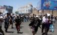 Protestos anti-houthi correm para fugir de bombas de gás lacrimogêneo disparadas por policiais aliados aos houthis em Taiz, no centro do Iêmen