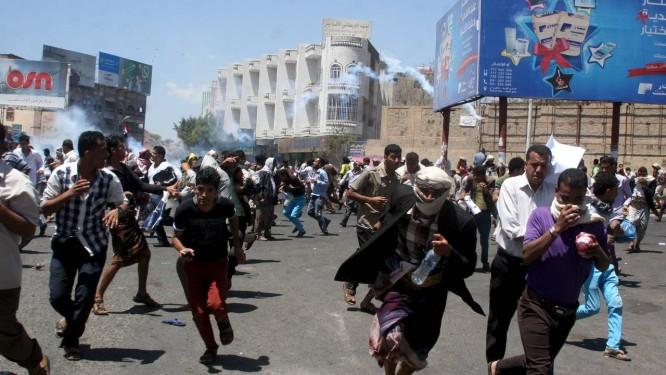 Protestos anti-houthi correm para fugir de bombas de gás lacrimogêneo disparadas por policiais aliados aos houthis em Taiz, no centro do Iêmen Foto: Anees Mahyoub / REUTERS