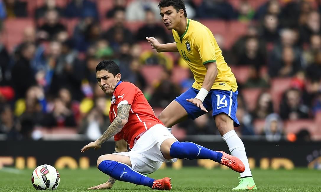 Thiago Silva faz a marcação sobre o jogador chileno durante o amistoso Dylan Martinez / REUTERS