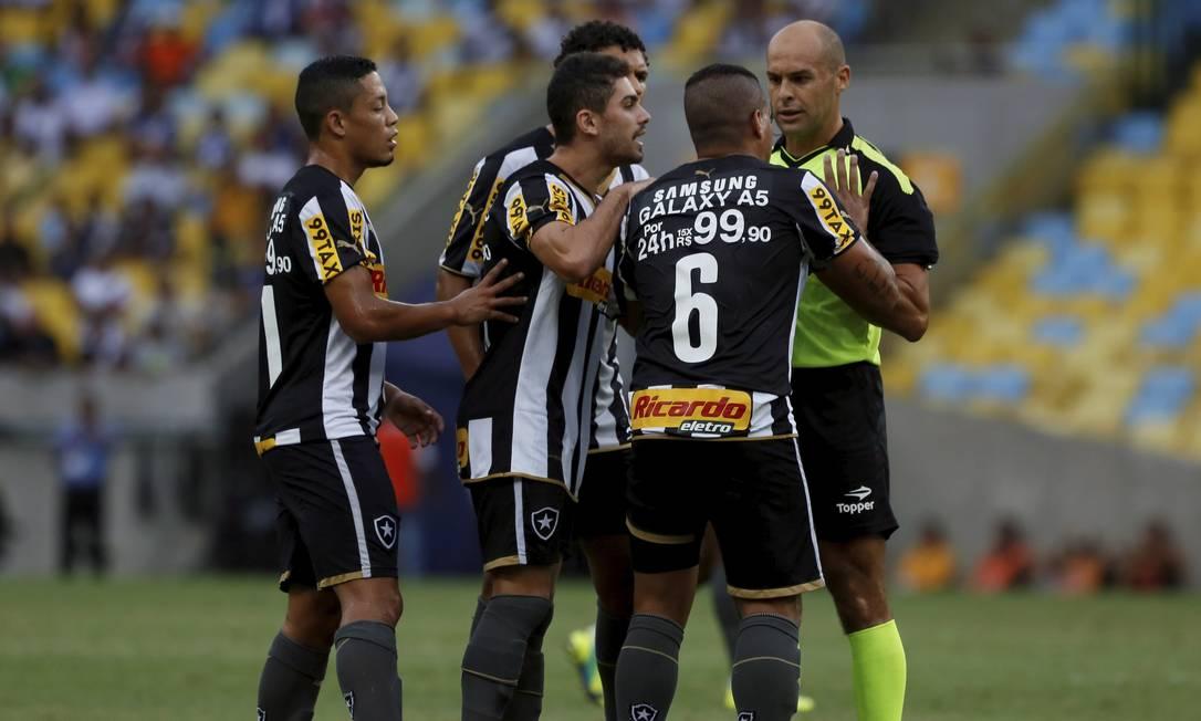 Jogadores do Botafogo pressionam o árbitro Grazianni Maciel, cobrando cartão amarelo para o adversário, em lance de falta Marcos Tristão / Agência O Globo