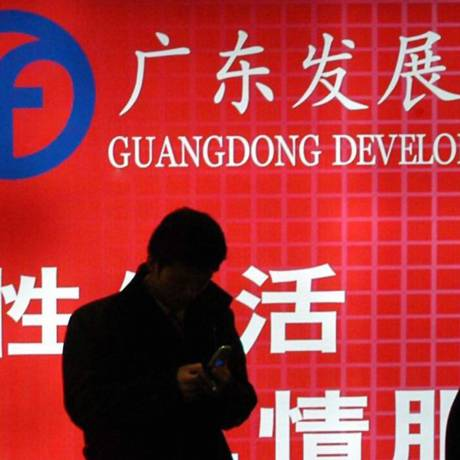 Pedestres passam em frente ao anúncio de um banco em Pequim Foto: Bloomberg News