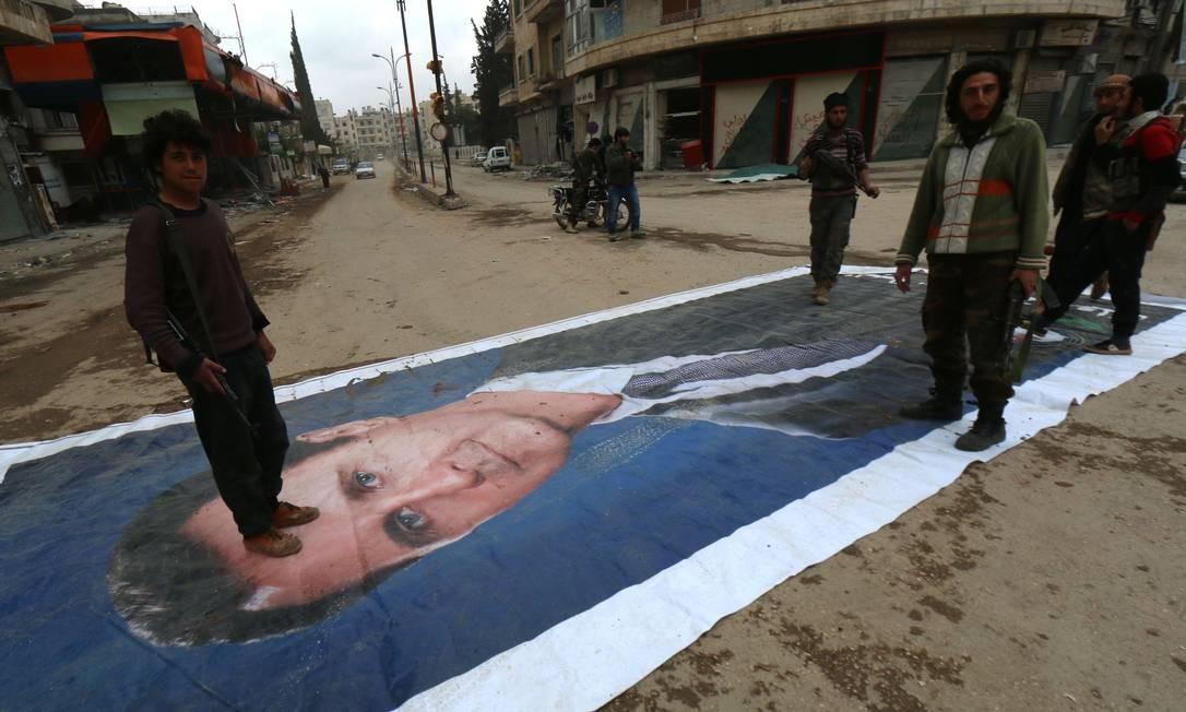 Jihadistas pisam em retrado de Bashar al-Assad, presidente sírio, na cidade de Idlib Foto: AFP