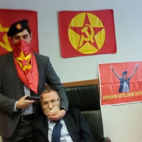 Integrante do grupo radical turco Frente Revolucionária pela Libertação Popular aponta arma para a cabeça do promotor Mehmet Selim Kiraz, que investiga o caso da morte do estudante Berkin Elvan, que passou 269 dias em coma após ser ferido em um protesto em 2013. O promotor foi sequestrado em pleno local de trabalho pelo grupo Foto: - / AFP