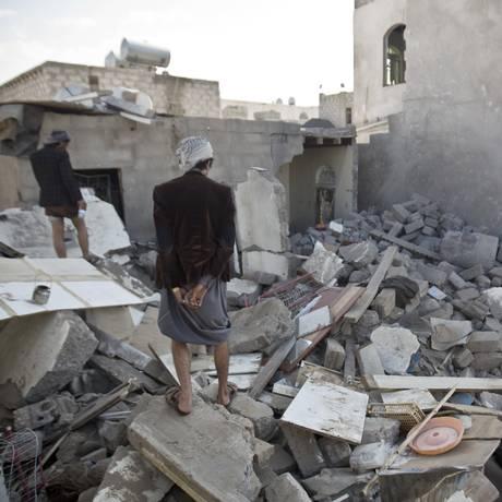 Moradores da capital iemenita, Sanaa, andam entre os destroços das casas destruídas pelos ataques aéreos. Companhias aéreas são aconselhadas a evitar voos sobre o país Foto: Hani Mohammed / AP