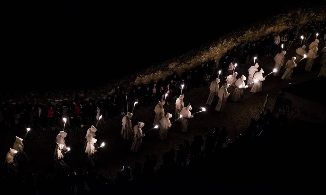 """Integrantes da irmandade """"Cristo da Boa Morte"""" carregam tochas em procissão na cidade de Zamora Andres Kudacki / AP"""