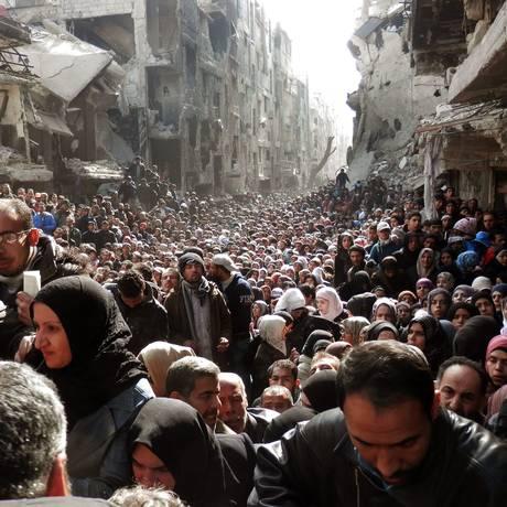 Foto de agência da ONU mostra refugiados de Yarmuk recebendo ajuda humanitária após bombardeios em Damasco, em 2014 Foto: United Nation Relief and Works Agency / AP