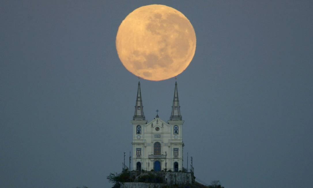 Muitas vezes, fotógrafos criam imagens que enganam observadores menos atentos. Custodio Coimbra, por exemplo, mostra a lua apoiada nas torres da Igreja da Penha Foto: Custódio Coimbra / Agência O Globo