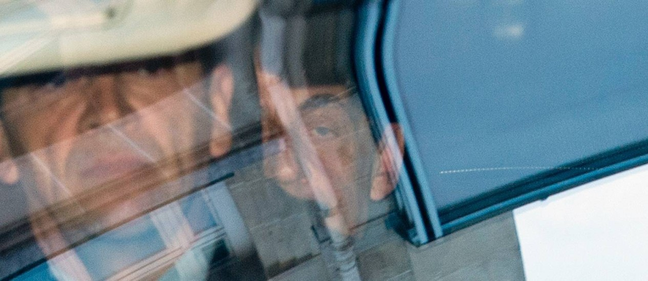 """Processo. Nicolas Sarkozy (ao fundo) chega ao tribunal para audiência na qual ele foi declarado """"testemunha assistida"""" no caso de pagamento irregular de multa por exceder limite de gastos na última campanha à Presidência francesa Foto: MIGUEL MEDINA/AFP"""