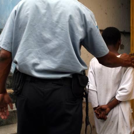 Menor é conduzido por policial após praticar assalto: relação entre redução da maioridade e queda na violência não é garantida Foto: Lucíola Villela / Lucíola Villela/13-12-2006