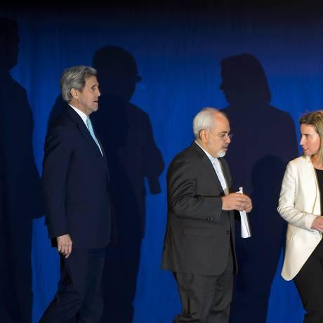 Kerry, o chanceler iraniano, Javad Zarif, e a chefe da UE para política externa, Federica Mogherini: acordo em Lausanne Foto: FABRICE COFFRINI / AFP