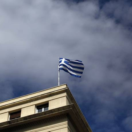 Bandeira da Grécia em um prédio em Atenas. Em crise, país levanta temores de calote no dia 9 de abril Foto: Kostas Tsironis / Bloomberg