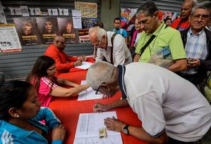 Firmas. Venezuelanos assinam petição pedindo o fim das sanções americanas Foto: FEDERICO PARRA/AFP