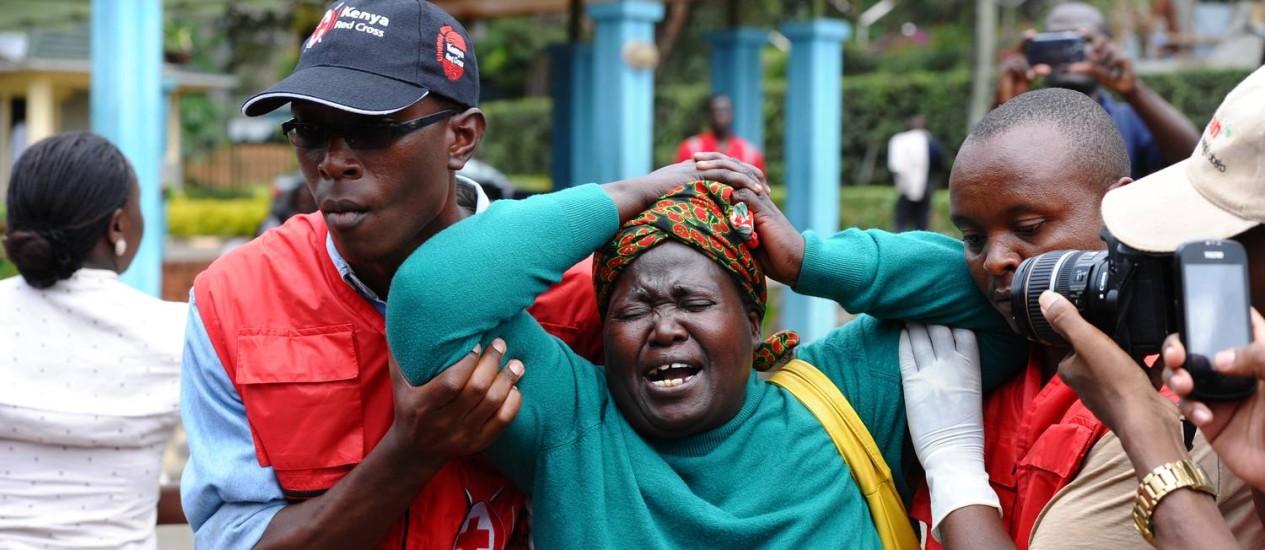 """Equipe da Cruz Vermelha no Quênia ampara mulher que reconheceu cadáver de parente entre as vítimas do ataque. Al-Shabaab ameaçou realizar """"novo banho de sangue"""" no país Foto: Stringer / AP"""
