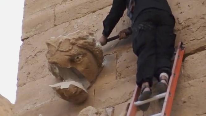Em imagem retirada do vídeo divulgado pelo Estado Islâmico, jihadista em escada destrói escultura com golpes de marreta Foto: Uncredited / AP