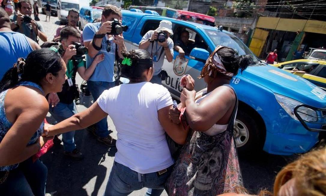 Terezinha de Jesus, mãe do menino Eduardo, é contida por amigos ao passar por policiais Foto: Marcia Foletto