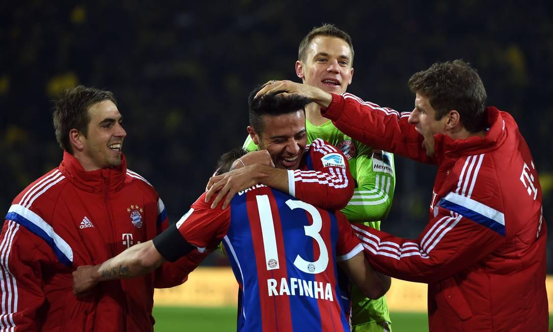 O brasileiro Rafinha é abraçado após a vitória do Bayern sobre o Borussia Dortmund PATRIK STOLLARZ / AFP